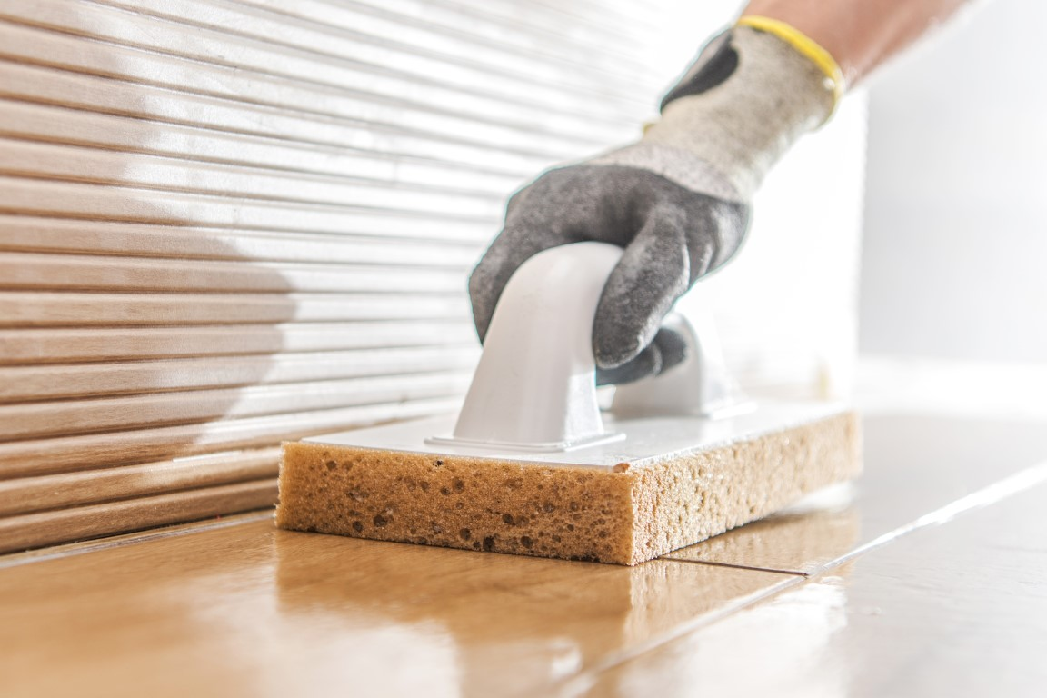 Professional cleaner cleaning tiles during construction project